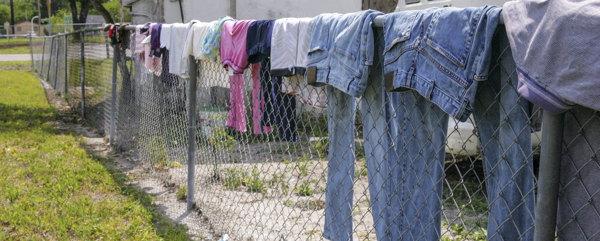 Clothes hang on a chain-link fence to dry