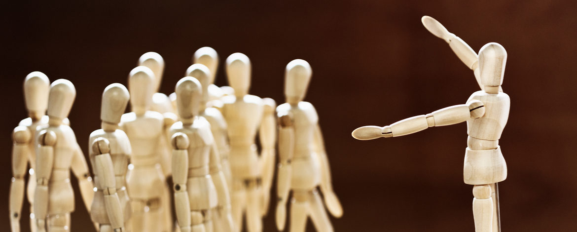 A small wooden figure stands on a platform in front of a crowd of similiar puppets, apparently making a speech to them.